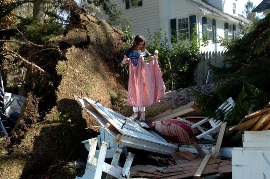 Alexandra Aiello tries to save some items from her play house on Park Avenue which was destroyed when a large pine tree fell on it, in Greenwich, Tuesday, March 16, 2010. Photo: Helen Neafsey / Greenwich Time