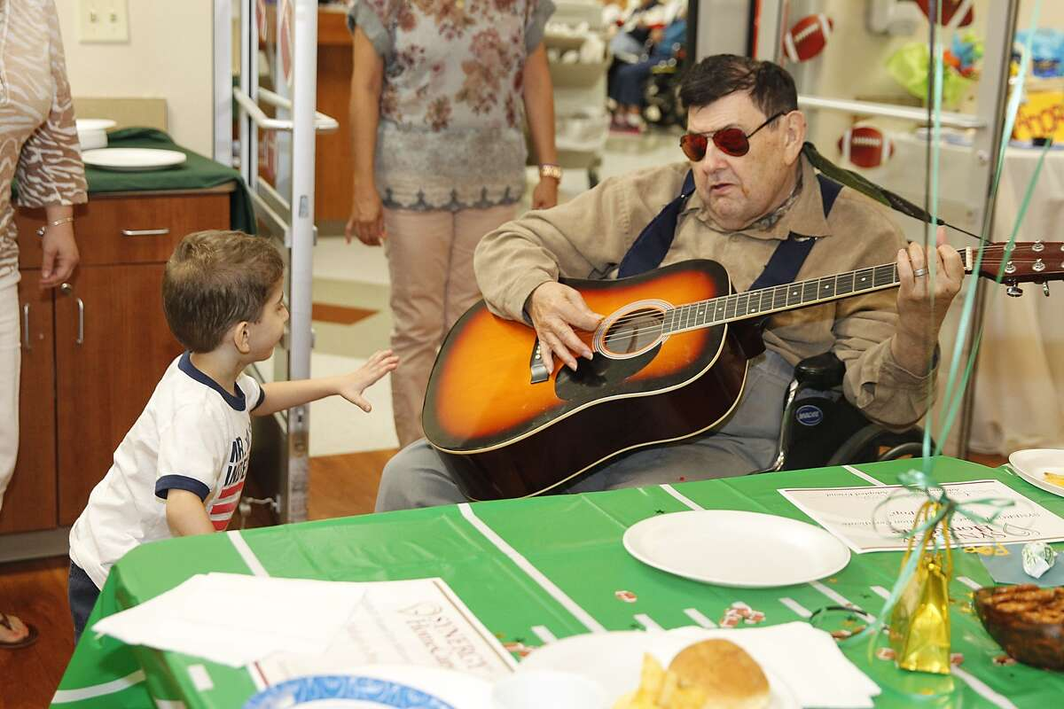Legend Oaks resident Henry Davidson, aka Elvis, entertains Liam Haselden, 5, at the Adopt-a-Pop luncheon/ice cream social at Legend Oaks Rehabilitation and Nursing Care Center in Katy earlier this summer.