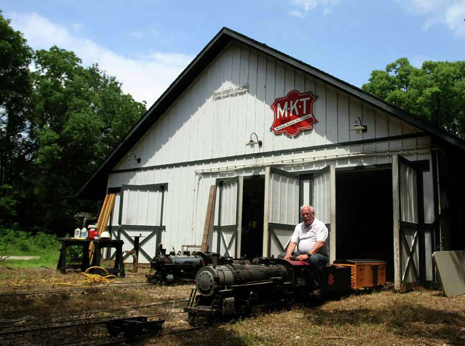 Dr. Mark Bing sits on one of the steam engines that pulls his miniature trains down rails he laid out around his Katy home. Photo: Jayme Fraser