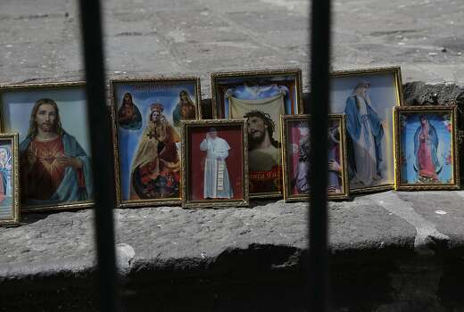 This June 14, 2015 photo shows framed images of Catholic icons on a street in downtown Quito, Ecuador. Pope Francis will encounter on his South American tour indigenous people whose traditions date back centuries to even before European priests brought Christianity to the New World. (AP Photo/Dolores Ochoa) Photo: Dolores Ochoa, Associated Press