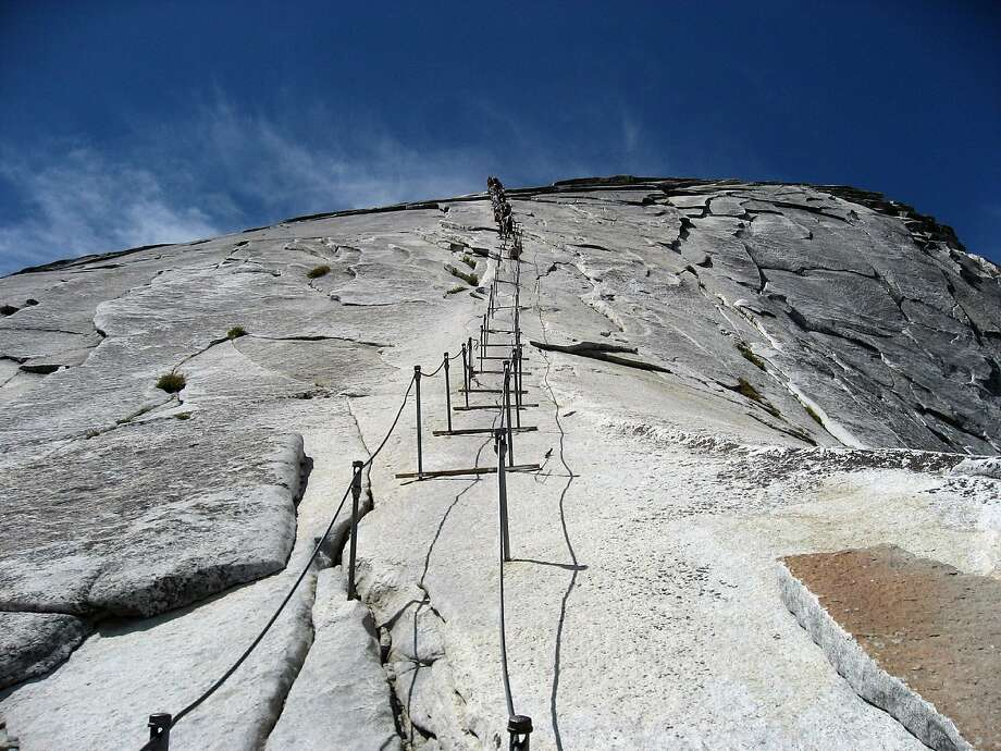 Hikers enjoy climbing alongside the cables on Half Dome during the summer of 2009.  A group is fighting Yosemite National Parks policy that limits the number of hikers on the final 400-foot climb up Half Dome. They say Americans have a right to freely enjoy nature. The park service began limiting the number of hikers on the enormous sliced-in-half granite dome in 2010 to combat regular bottlenecks. Photo: Bethany Gediman, Special To The Chronicle