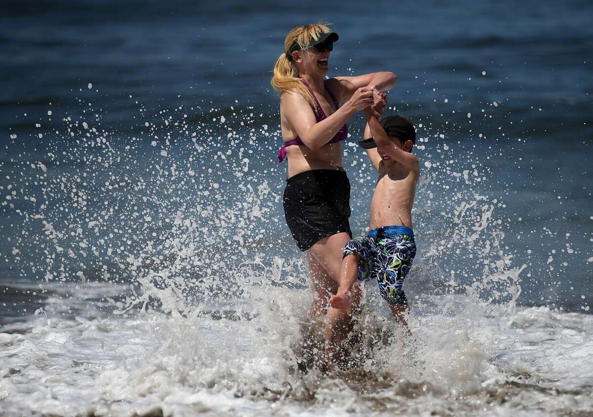 Beachgoers play in the surf at Ocean Beach on May 13, 2014 in San Francisco, California. The San Francisco Bay Area experienced record temperatures with S.F. reaching 90, breaking the old record of 87 set in 1927.