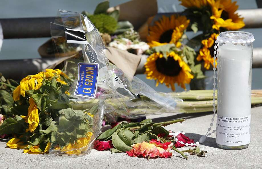 Flowers and a candle lay on the ground following a vigil for Kathryn Steinle, Monday, July 6, 2015, on Pier 14 in San Francisco. Steinle was gunned down while out for an evening stroll at Pier 14 with her father and a family friend on Wednesday, July 1. (AP Photo/Beck Diefenbach) Photo: Beck Diefenbach, Associated Press