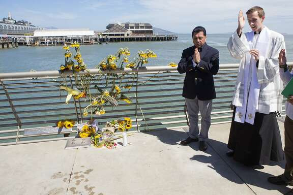 Father Cameron Faller, right, and Julio Escobar, of Restorative Justice Ministry, conduct a vigil for Kathryn Steinle, Monday, July 6, 2015, on Pier 14 in San Francisco. Steinle was gunned down while out for an evening stroll at Pier 14 with her father and a family friend on Wednesday, July 1. (AP Photo/Beck Diefenbach)
