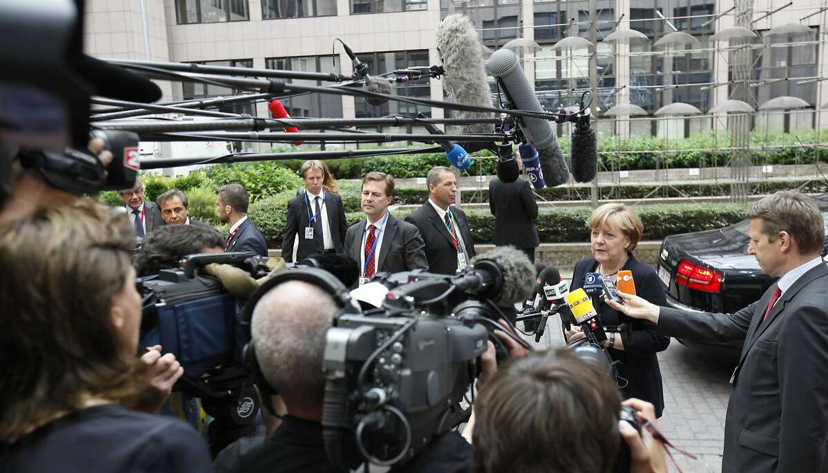 German Chancellor Angela Merkel speaks with the media as she arrives for an emergency summit of eurozone heads of state or government at the EU Council building in Brussels on Tuesday, July 7, 2015. Greek Prime Minister Alexis Tsipras was heading Tuesday to Brussels for an emergency meeting of eurozone leaders, where he will try to use a resounding referendum victory to eke out concessions from European creditors over a bailout for the crisis-ridden country. (AP Photo/Francois Walschaerts)