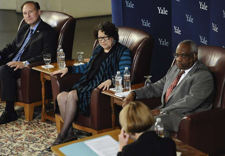 U.S. Supreme Court justices Samuel Alito, Jr., left, Sonia Sotomayor, second from left, and Clarence Thomas, second from right, listen to a question by law professor Kate Stith, right foreground, during a conversation at Yale University, Saturday, Oct. 25, 2014, in New Haven, Conn. Thomas graduated from Yale Law School in 1974, Alito in 1975 and Sotomayor in 1979. The six other Supreme Court justices all attended Harvard's law school.(AP Photo/Jessica Hill) Photo: Jessica Hill, Associated Press