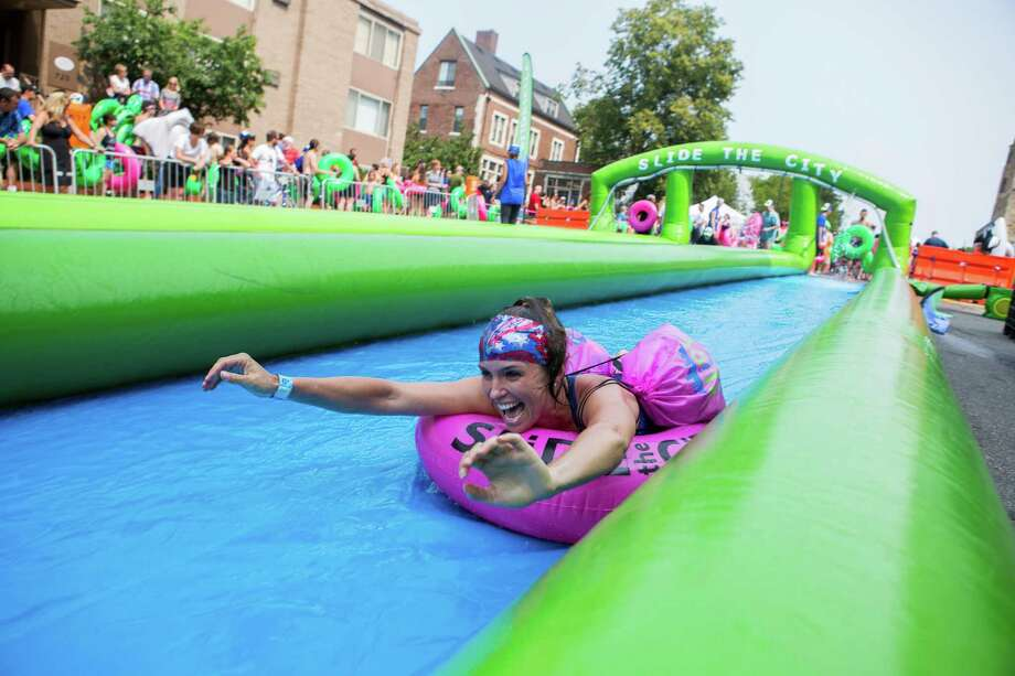 In this July 4, 2015, photo, a woman smiles as she slides along South State Street on the University of Michigan campus during Slide the City, in Ann Arbor, Mich. (Dominic Valente/Detroit News via AP)  Photo: Dominic Valente, AP / Detroit News