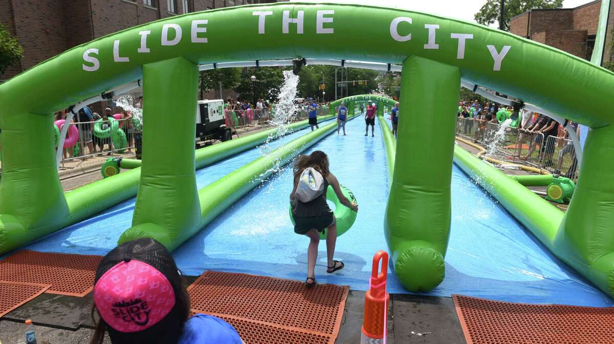 In this July 4, 2015, photo, riders slide down South State Street on the University of Michigan campus during Slide the City, in Ann Arbor, Mich.