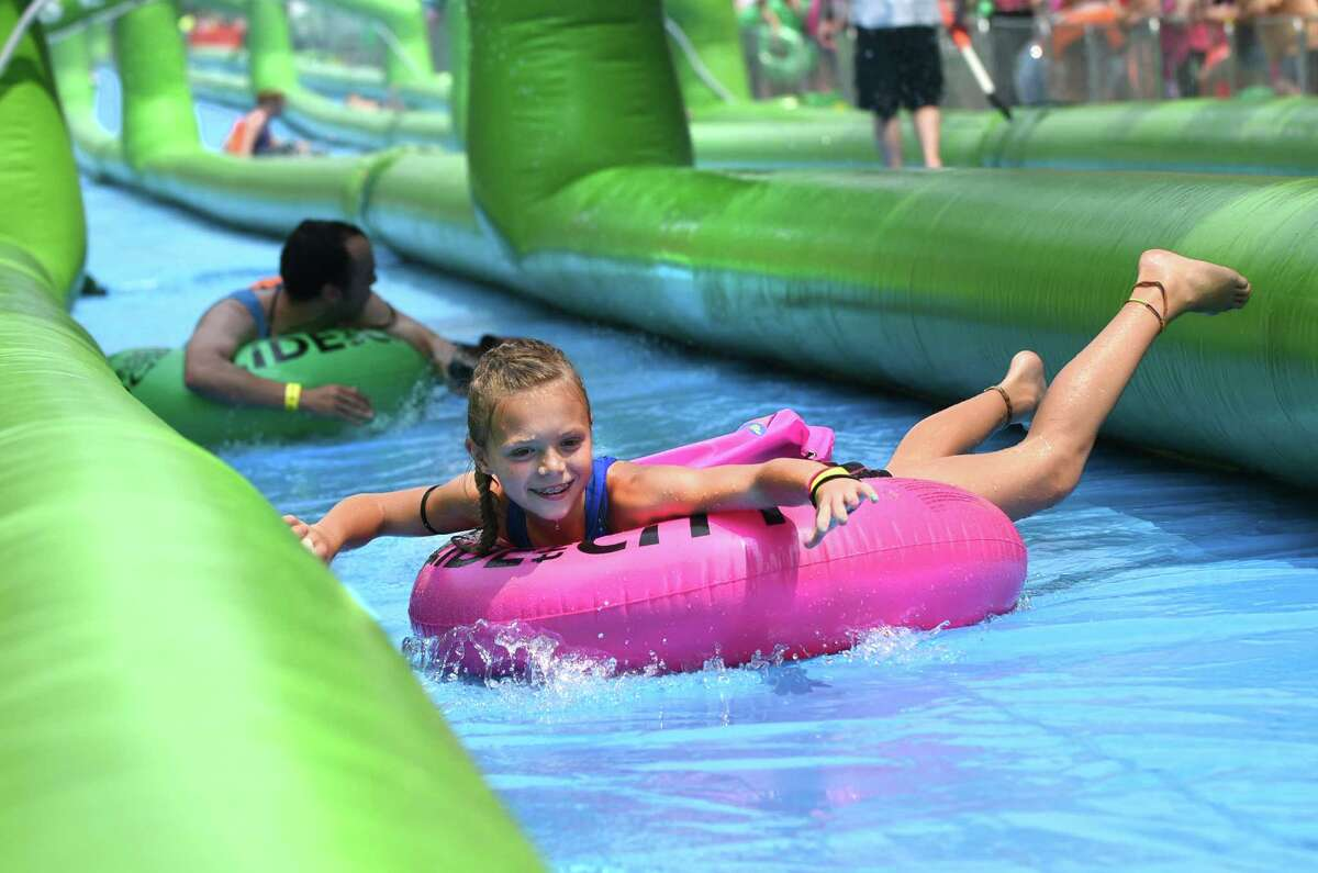 In this July 4, 2015, photo, Ericka Sauld, 9, of Ann Arbor, smiles as she slides along South State Street on the University of Michigan campus during Slide the City, in Ann Arbor, Mich.