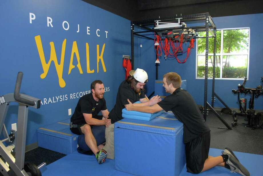 Trainer Jacob Calhoun, left, helps Brooks Dremely with hip exercises with assistance from Austin Reed, right, at Project Walk Houston. Photo: George Wong / Freelance