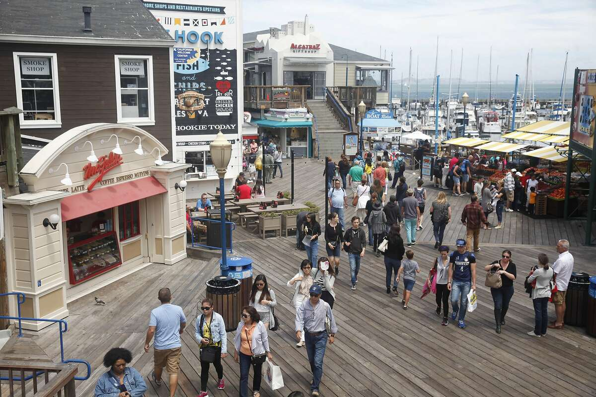 People visiting Pier 39 walk past shops on Pier 39 on Tuesday, July 7, 2015 in San Francisco, Calif.