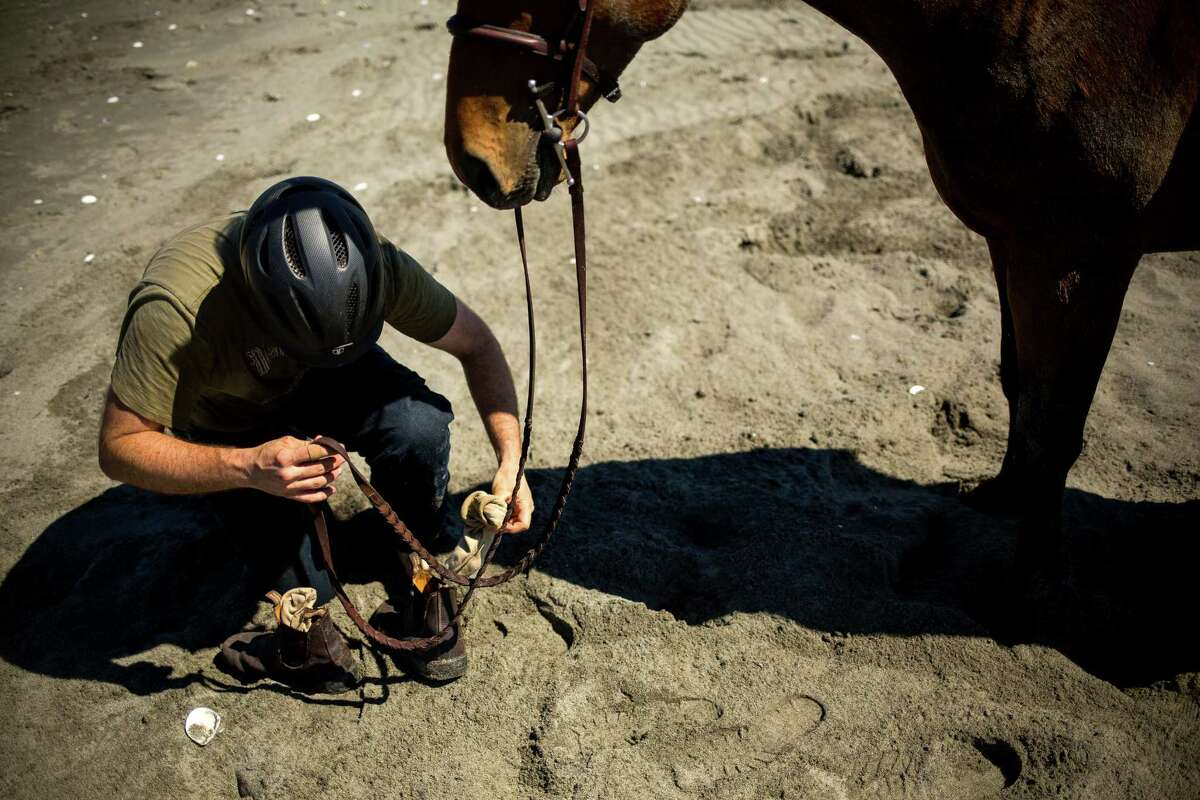 Riders gear up before taking their steeds into the waters of Useless Bay Friday, July 3, 2015, on Whidbey Island, Washington.