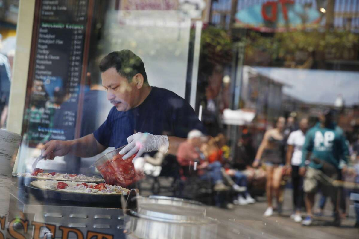 Javier Medina,crepe maker, makes crepes in a window at the Crepe Cafe while visitors at Pier 39 are reflected in the glass of the window on Tuesday, July 7, 2015 in San Francisco, Calif.