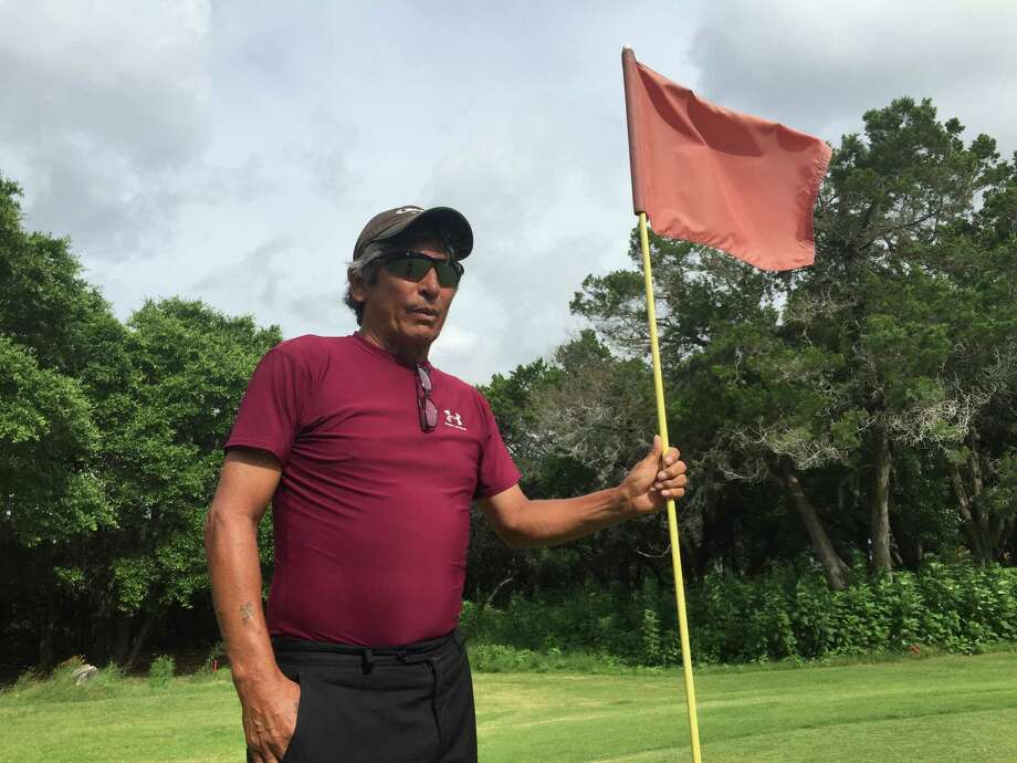 "Frankie Gonzales holds the pin at the 237-yard, par-4 14th hole at Lakeside Golf Club at Canyon Lake. Gonzalez has cared eight holes-in-one on this hole, techically called an ""albatross."" Photo: Roy Bragg /San Antonio Express-News"