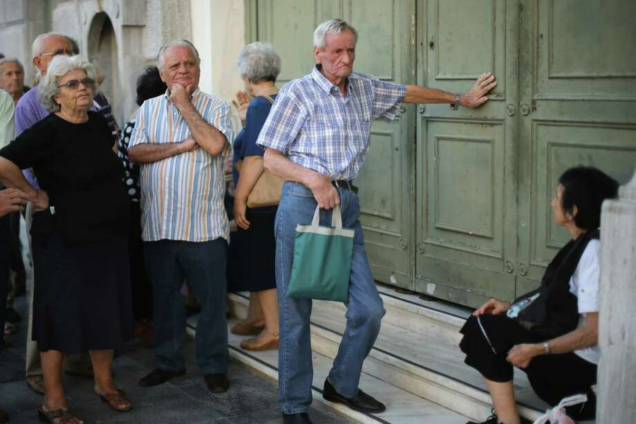 Senior citizens queue up to collect their pensions outside a National Bank of Greece branch in Kotzia Square on July 7, in Athens. Greece has Sunday deadline to prevent a fiscal diaster.   (Photo by Christopher Furlong/Getty Images) Photo: Christopher Furlong, Staff / 2015 Getty Images