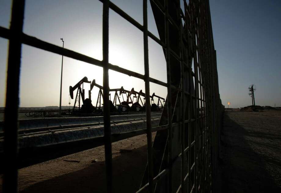 FILE - In this May 28, 2015 file photo, oil pumps work in the desert oil fields of Sakhir, Bahrain. A slew of global economic and geopolitical factors are working to pummel the price of oil and set up U.S. drivers for very low gasoline prices later this year. (AP Photo/Hasan Jamali, File) Photo: Hasan Jamali, STR / AP