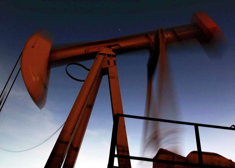 An oil pump works in the desert oil fields of Bahrain. Crude futures settled in New York on Wednesday at $50.28 barrel, down $2.86. Photo: Hasan Jamali, STR / AP