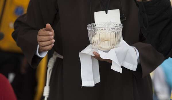Priests give the communion during an open-air mass officiated by Pope Francis at Bicentennial Park in Quito, on July 7, 2015. Pope Francis celebrates his second open air mass in as many days in Ecuador on Tuesday, this time in Quito, the capital city roiled for the past month by anti-government protests. Photo: VLADIMIR RODAS, AFP/Getty Images