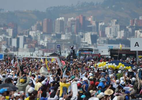 Pope Francis is seen amid hundreds of faithful before the start of an open-air mass at the Bicentennial Park in Quito, Ecuador, on July 7, 2015. The visit of the Argentine-born pontiff comes amid widespread unrest over the socialist policies of President Rafael Correa --who is expected to attend the mass. Photo: VINCENZO PINTO, AFP/Getty Images