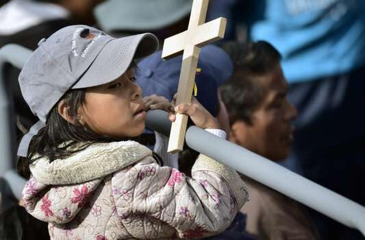 A child waits for the start of an open-air mass by Pope Francis at the Bicentennial Park in Quito, Ecuador, on July 7, 2015. Pope Francis celebrates his second open air mass whilst hundreds of thousands of faithful were expected to turn out to see the Argentine-born pontiff, who offered a message of harmony and familial unity at an open air mass on the eve, in Guayaquil. Photo: RODRIGO BUENDIA, AFP/Getty Images
