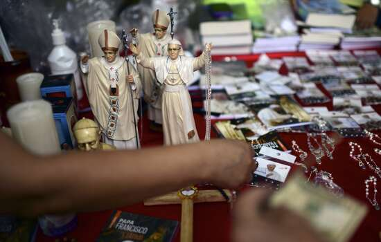 People buy memorabilia of Pope Francis in Quito, on July 7, 2015. Pope Francis celebrated his second open air mass in as many days in Ecuador, this time in Quito, the capital city roiled for the past month by anti-government protests. Photo: MARTIN BERNETTI, AFP/Getty Images