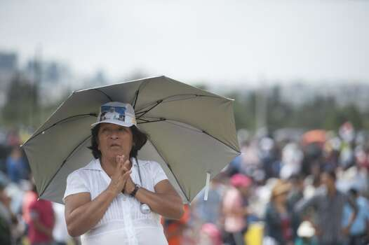 Faithful participate in an open-air mass officiated by Pope Francis at Bicentennial Park in Quito, on July 7, 2015. Pope Francis celebrates his second open air mass in as many days in Ecuador on Tuesday, this time in Quito, the capital city roiled for the past month by anti-government protests. Photo: VLADIMIR RODAS, AFP/Getty Images