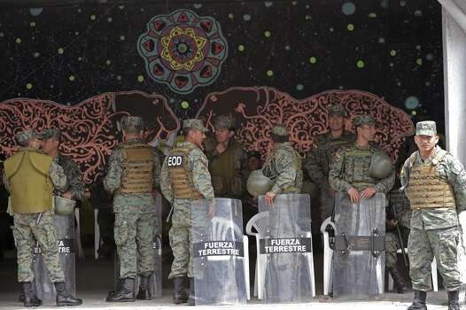 Militarized policemen take a rest whilst Pope Francis celebrates an open-air mass at the Bicentennial Park in Quito, Ecuador, on July 7, 2015. The visit of the Argentine-born pontiff comes amid widespread unrest over the socialist policies of President Rafael Correa --who is expected to attend the mass. Photo: VINCENZO PINTO, AFP/Getty Images