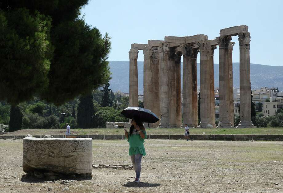 A tourist holds an umbrella to protect from the sun as she visits the Temple of Zeus in Athens, Tuesday, July 7, 2015. This is Greek tourism - July 2015 style - as the peak summer season in one of the world's most popular destinations is glitched by a financial crisis of frightening proportions. The World Travel and Tourism Council said tourism's direct contribution to the Greek economy was more than 29 billion euros in 2014, accounting for just over 17 percent of the country's GDP.  Photo: Spyros Tsakiris, STR / AP