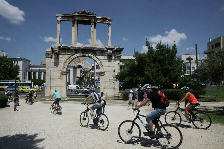Tourists ride bicycles next to Andrian's Arch  in Athens, Tuesday, July 7, 2015.  Photo: Spyros Tsakiris, STR / AP