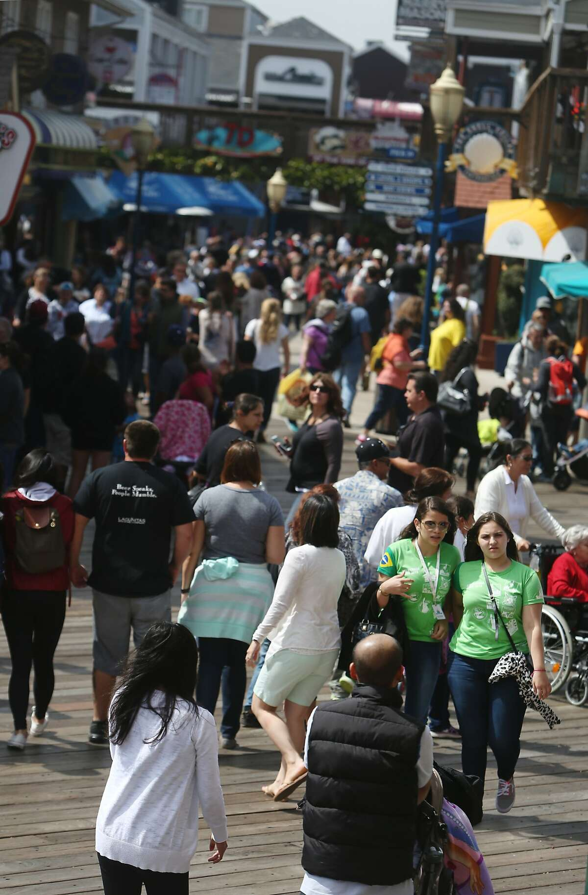 Maria Clara Sampaio (green shirts l to r) and Amanda Farache both of Brazil, navigate their way through the crowd walking on Pier 39 during a visit on Tuesday, July 7, 2015 in San Francisco, Calif.