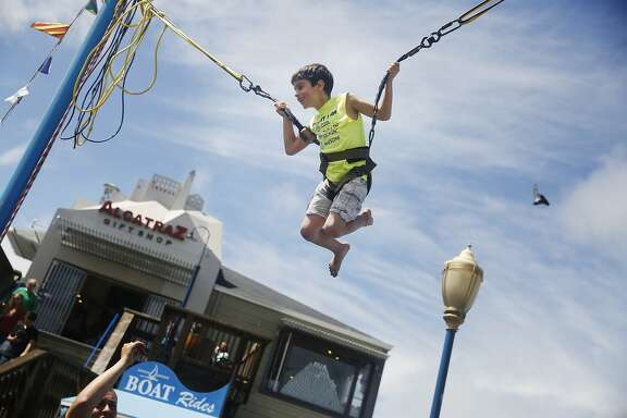 Thomas Thorpe, 7, of Willows, bounces in the air on the Bungee Trampoline on Pier 39 during a visit on Tuesday, July 7, 2015 in San Francisco, Calif.