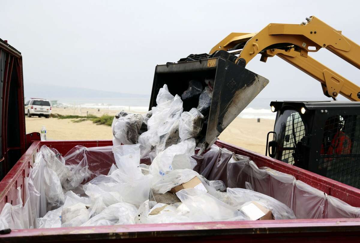 Contaminated bags of sand and oil are loaded into a dumpster in Manhattan Beach, Calif. on Thursday, May 28, 2015. Popular beaches along nearly 7 miles of Los Angeles-area coastline are off-limits to surfing and swimming after balls of tar washed ashore. The beaches along south Santa Monica Bay appeared virtually free of oil Thursday morning after an overnight cleanup, but officials aren't sure if more tar will show up. (AP Photo/Nick Ut)