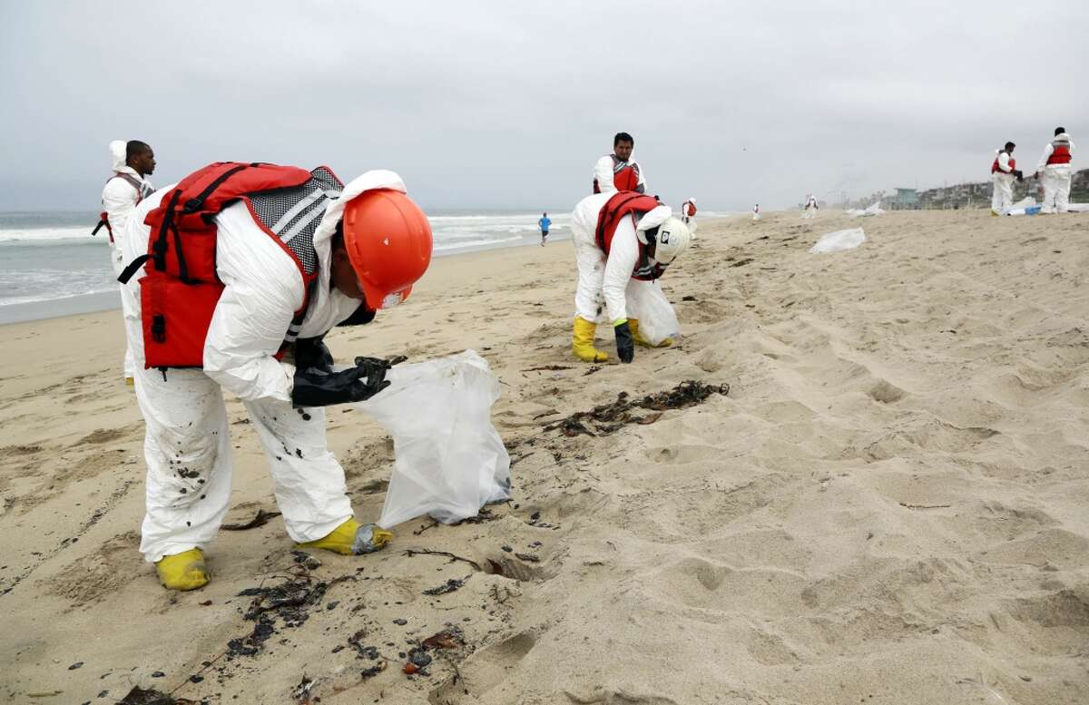 A crew cleans up a beach after balls of tar washed ashore in Manhattan Beach, Calif. on Thursday, May 28, 2015. Popular beaches along nearly 7 miles of Los Angeles-area coastline are off-limits to surfing and swimming after balls of tar washed ashore. The beaches along south Santa Monica Bay appeared virtually free of oil Thursday morning after an overnight cleanup, but officials aren't sure if more tar will show up. (AP Photo/Nick Ut)