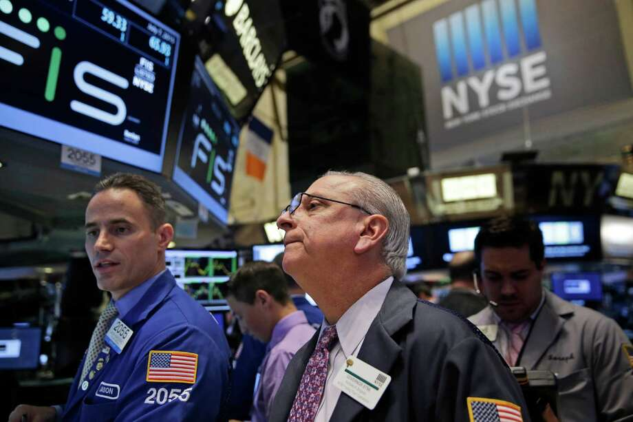 Floor Governor Nicholas Brigandi, center, works with traders on the floor at the New York Stock Exchange in New York, Tuesday, July 7, 2015. Global stocks mostly fell on Tuesday as Greece's spiraling crisis kept investors on edge and as Chinese markets dropped despite government intervention. (AP Photo/Seth Wenig) ORG XMIT: NYSW102 Photo: Seth Wenig / AP