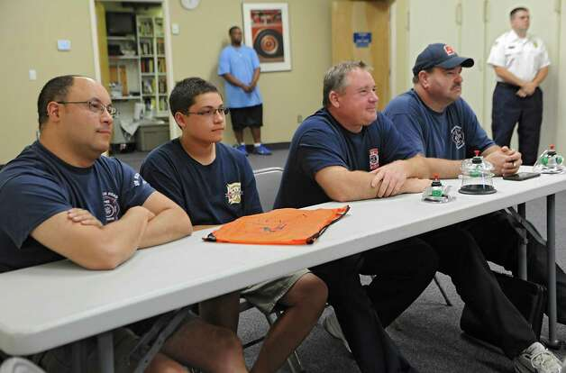 From left, John and son Zachary Palaszynski, 15, of Loudonville, Chip Heinbach of Loudonville and David Dalhein of Colonie listen as veterinarian Amanda Little of Shaker Veterinary Hospital teaches firefighters how to put oxygen masks on pets at the Shaker Road-Loudonville Fire Department on Tuesday, July 7, 2015 in Colonie, N.Y.  (Lori Van Buren / Times Union) Photo: Lori Van Buren / 00032529A