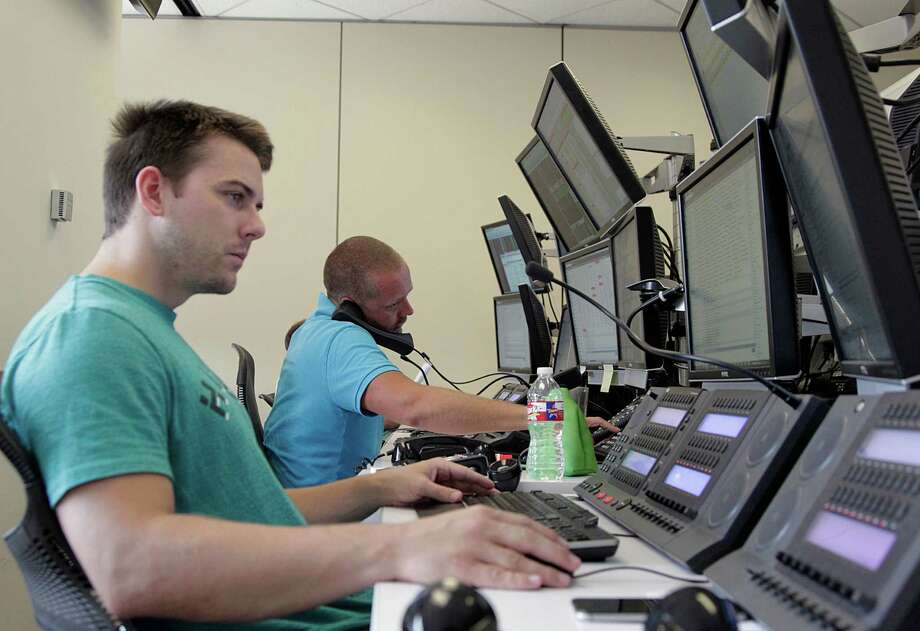 Daniel Adamek left, and Jamie Spicer right, brokering oil commodities on the OTC Global Holdings Aalpha Energy Desk Tuesday, July 7, 2015, in Houston.  ( James Nielsen / Houston Chronicle ) Photo: James Nielsen, Staff / © 2015  Houston Chronicle