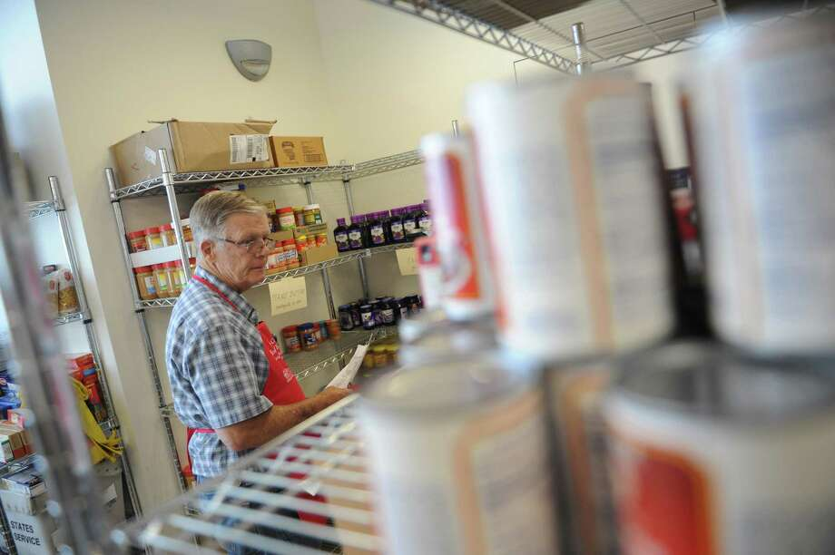 Volunteer Richard Greene helps a customer shop in the food pantry at the new New Covenant House of Hospitality in Stamford, Conn. Sunday, July 7, 2015.  New Covenant recently relocated from its 2,200 sq. ft. space in the basement of the Yearwood center to a new 8,000 sq. ft. building across the street.  The facility includes a state-of-the-art soup kitchen, spacious dining hall, food pantry, and will soon have other amenities available for use like washers and dryers, showers and a computer lab. Photo: Tyler Sizemore / Hearst Connecticut Media / Greenwich Time