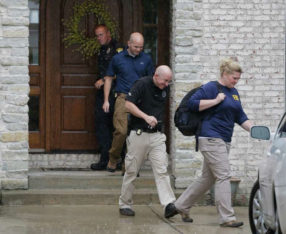 Federal authorities walk out of the home of Subway restaurant spokesman Jared Fogle on Tuesday. FBI agents and Indiana State Police removed electronics from the property. Photo: Michael Conroy, STF / AP