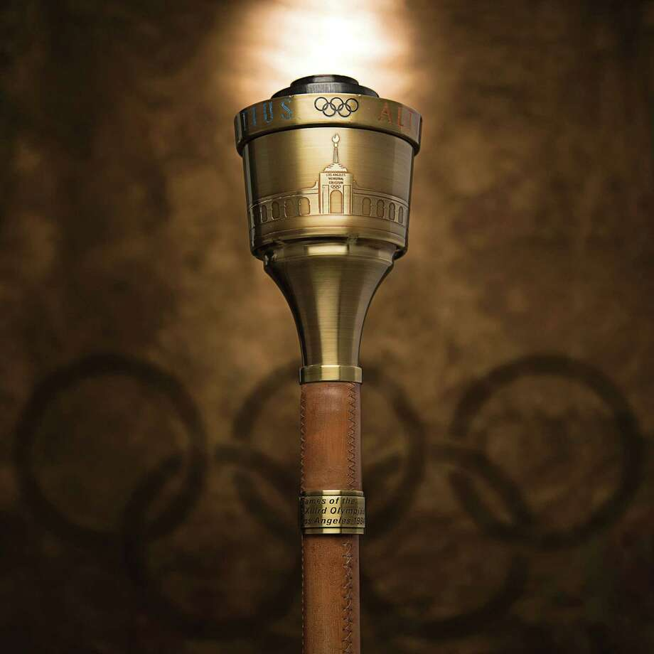 In this undated photo provided by Heritage Auctions, the 1984 Summer Olympics Torch that Bruce Jenner carried through Lake Tahoe, Nevada is shown. The 24-inch torch, featuring a brass finish and wood handle, is being offered by Heritage Auctions on July 30, 2015, at its Platinum Night Sports Auction in Chicago. It is the first significant piece of Jenner memorabilia to go to auction since the winner of the 1976 Olympic Decathlon Gold Medal became Caitlyn Jenner. (Heritage Auctions via AP) ORG XMIT: NYR401 / Heritage Auctions
