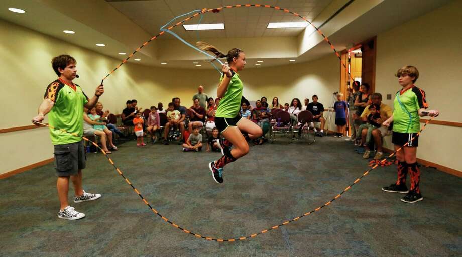 Jumper Olivia Key (center), 13, of The Jumping Dragons jump rope team demonstrates her jumping skills with coach Bobby Barrera (left) and Brinley Barrera (right) in front of an audience at Cody Library  on Tuesday, July 7, 2015. Coach Barrera has been teaching jump roping for the past 16 years and the group performs at various events including Spurs games and at the Institute of Texan Culture's Folklife Festival. (Kin Man Hui/San Antonio Express-News) Photo: Kin Man Hui, Staff / San Antonio Express-News / ©2015 San Antonio Express-News