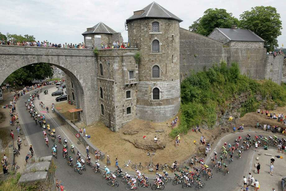 The pack makes its way past the Citadel of Namur, a fortress in the Belgian city, with some sections that date to 937. Photo: Laurent Cipriani, STR / AP