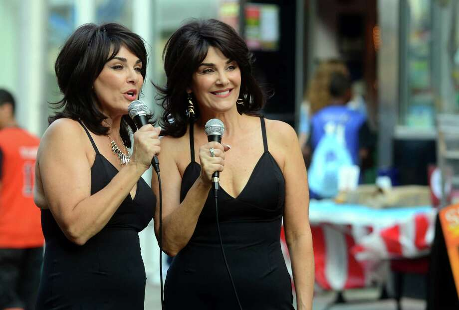 The Twice Baked Twins, Joy Paoletti, left, and Joy Vig, report during the Bluefish All-Star Block Party on Fairfield Avenue in downtown Bridgeport, Conn., on Tuesday July 7, 2015. Two bands performed at the party: the Jim Royle Drum Studio Steel Band Ensemble, from here in Bridgeport, and the Hartford-based jam band The McLovins. The festivities are part of the Atlantic League's All-Star Game which will be at the Ballpark at Harbor Yard on Wednesday night at 7 p.m. Photo: Christian Abraham / Hearst Connecticut Media / Connecticut Post