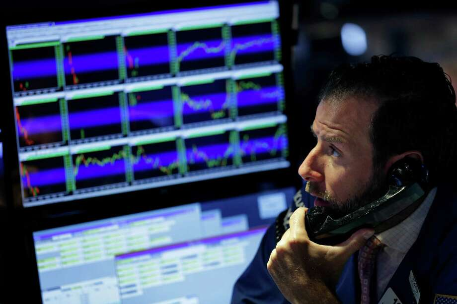 A trader works on the floor at the New York Stock Exchange in New York, Tuesday, July 7, 2015. Global stocks mostly fell on Tuesday as Greece's spiraling crisis kept investors on edge and as Chinese markets dropped despite government intervention. (AP Photo/Seth Wenig) Photo: Seth Wenig, STF / AP