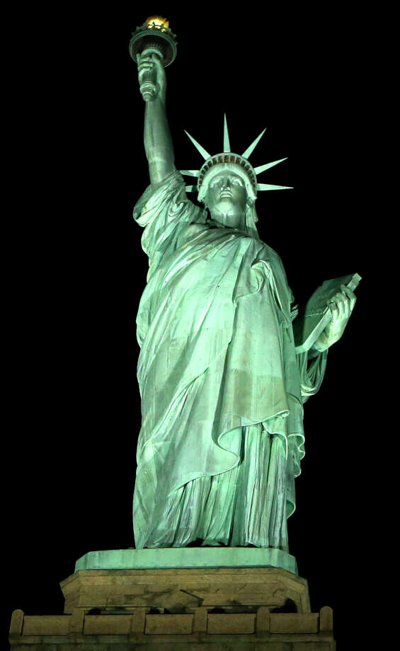 New light-emitting diodes or LEDs illuminate the Statue of Liberty on Liberty Island after the new system was turned on in New York, Tuesday, July 7, 2015. The system comes from Musco Lighting of Oskaloosa, Iowa. Musco systems are also in place at the Washington Monument, the White House and the Flight 93 National Memorial. (AP Photo/Kathy Willens) ORG XMIT: NYKW106 Photo: Kathy Willens