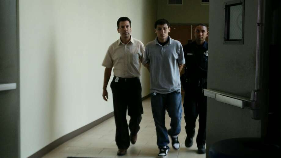 Police escort Jose Carrizales, 23, down a hall at the San Antonio Police headquarters downtown on Tuesday, July 7, 2015. Carrizales was arrested on a charge of murder in the May 24, 2015, shooting death of Dominic Spiller at an apartment complex in the 3800 block of West Avenue. Photo: Jacob Beltran /San Antonio Express-News