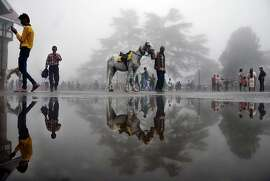 TOPSHOTS An Indian man walks with a horse past a puddle in the northern hill town of Shimla on July 7, 2015. AFP PHOTOSTR/AFP/Getty Images