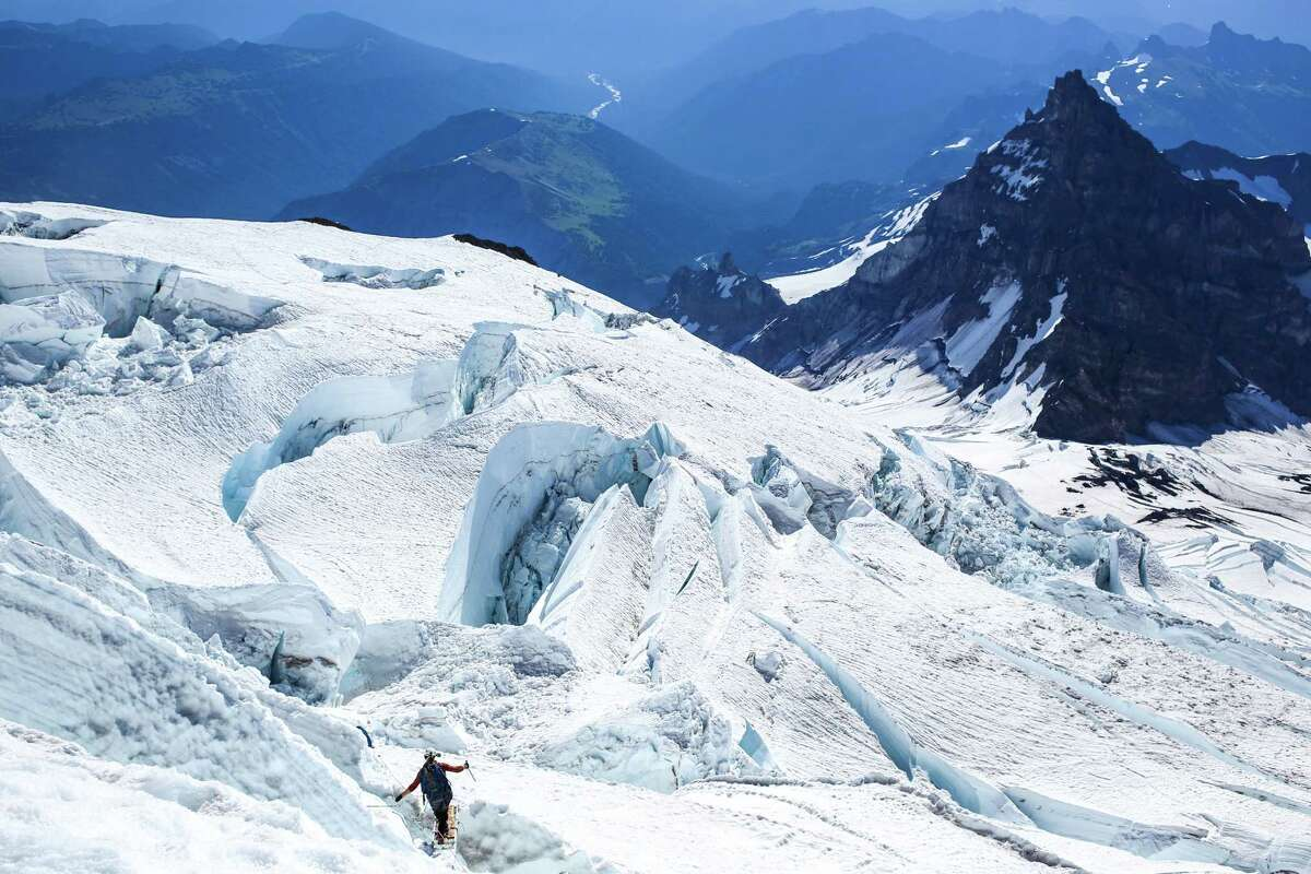 A climber negotiates a ladder placed over a crevasse on the Ingraham Glacier during a summit of Mount Rainier on June 30, 2015. The iconic Pacific Northwest volcano is a popular challenge for mountaineers. Weather conditions have made climbing routes challenging as climbers must negotiate gaping crevasses on the mountain.