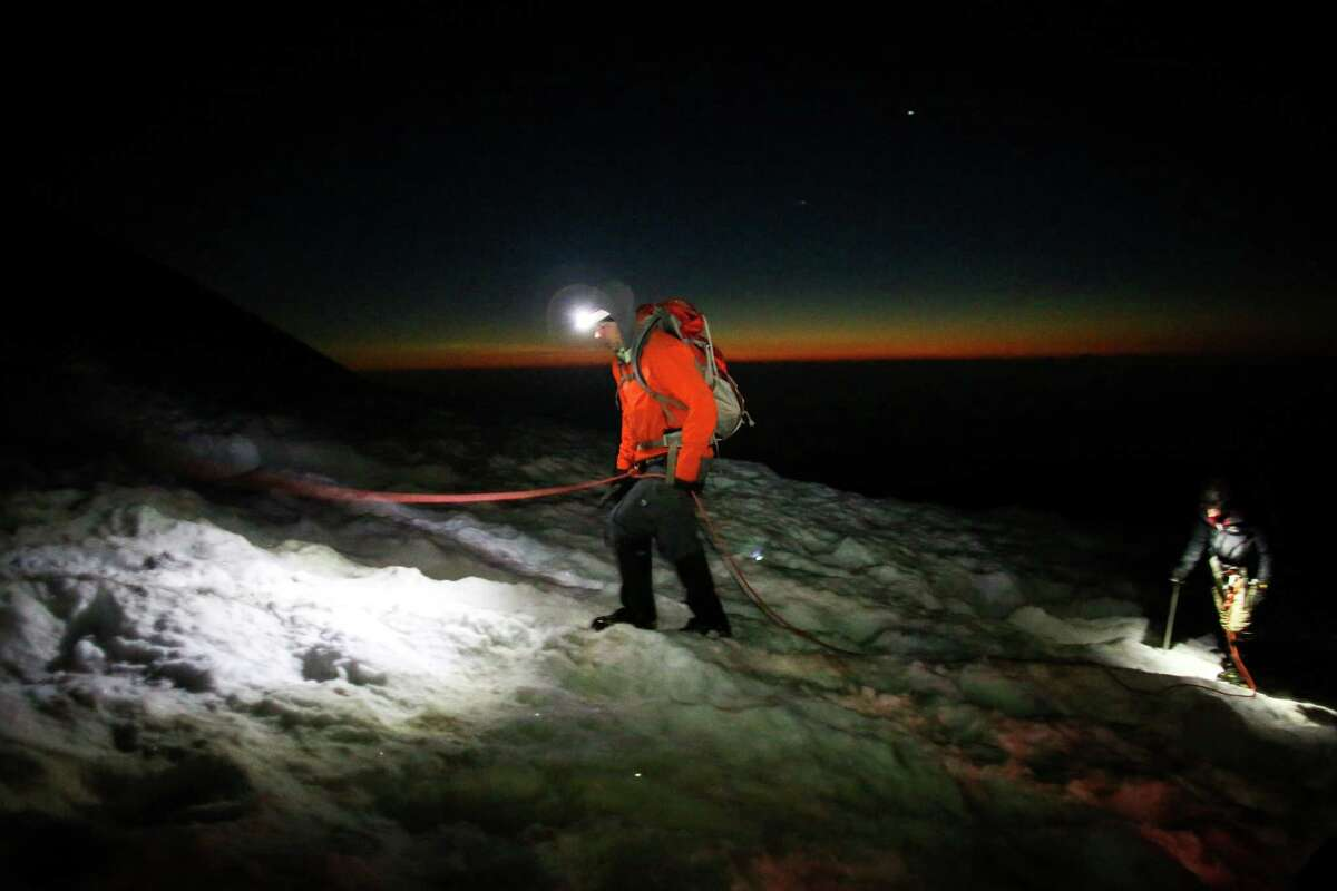 A climber uses a headlamp during the beginning of dawn near the top of Disappointmentment Cleaver as teams ascend Mount Rainier on June 30, 2015. The iconic Pacific Northwest volcano is a popular challenge for mountaineers.
