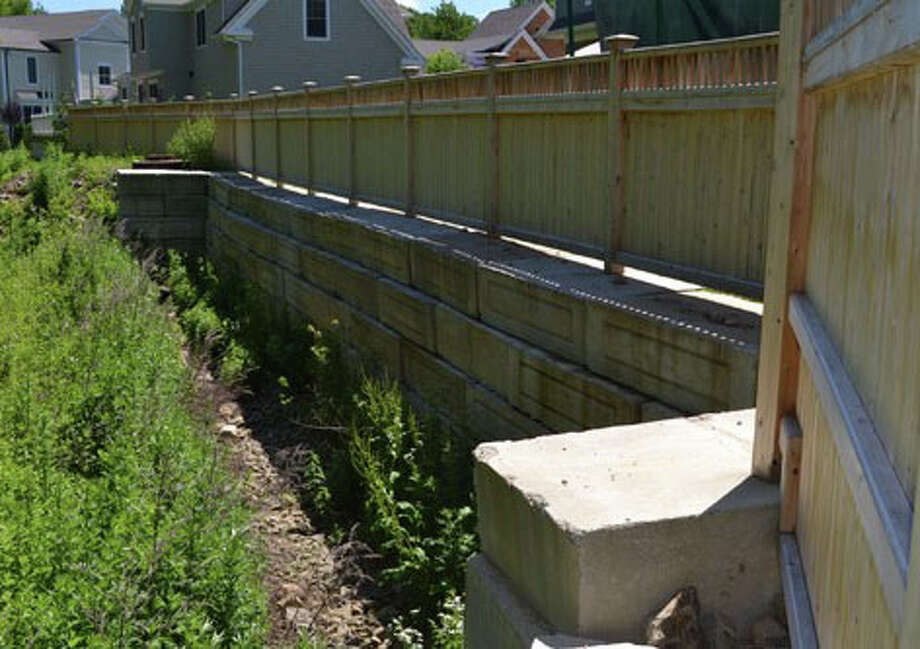 The retaining wall and stockade fence built behind homes at the upscale housing development known as the Reserve at Poplar Plains on Grassy Plains Road. Photo: Contributed / Contributed Photo / Westport News