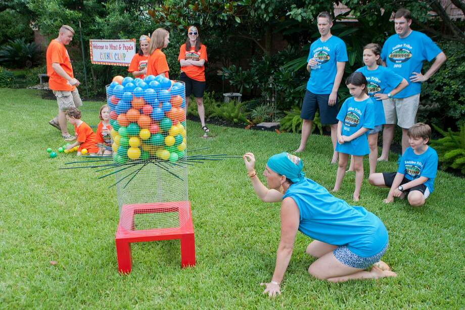 """Liz Goodman pulls a stick from the hive during a game at Cousin Camp, Frank and Lynda Bain's backyard celebration for their kids and grandkids.  The object here was to remove sticks from the bottom of the """"hive"""" without letting the balls or wasps fall out of the bottom. Photo: R. Clayton McKee, Freelance / © R. Clayton McKee"""